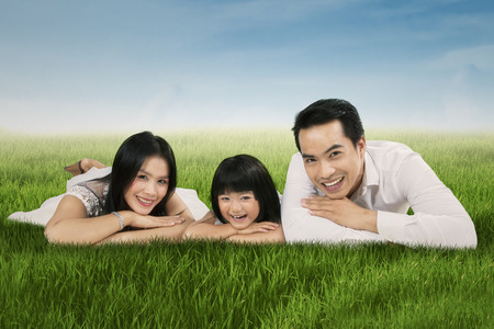 Portrait of happy asian family lying on grass and smiling at camera photo