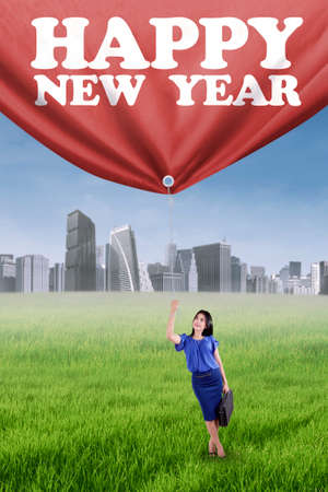 woman rope: Portrait of businessperson pulling a text of happy new year on the meadow