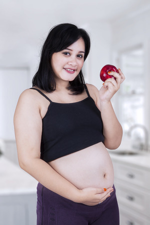 Portrait of pregnant woman smiling at camera while holding a red apple in the kitchen photo