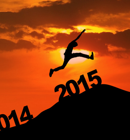 Man jumping over number of 2015 on the hill at sunset photo