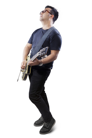 single songs: Portrait of young guitarist showing his talent by playing guitar, isolated over white