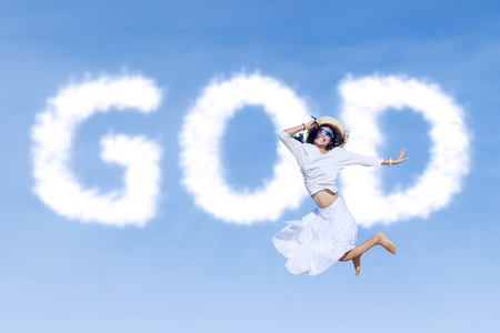 Excited asian woman is jumping with god clouds on the sky photo