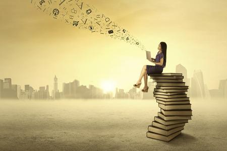 libros volando: Joven mujer sentada en libros durante el uso de ordenador portátil para enviar el mensaje Foto de archivo