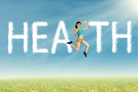 Sports woman jumping with clouds shape of health at sunny day photo