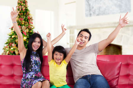 Hispanic family sitting on sofa and expressing happy to celebrate christmas day photo