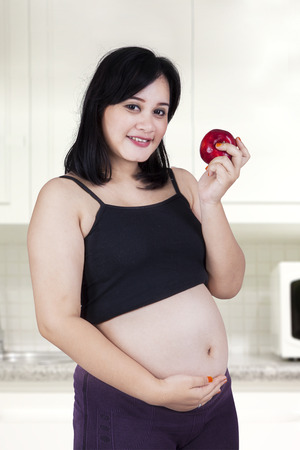 Young pregnant mother eating a red apple in the kitchen photo