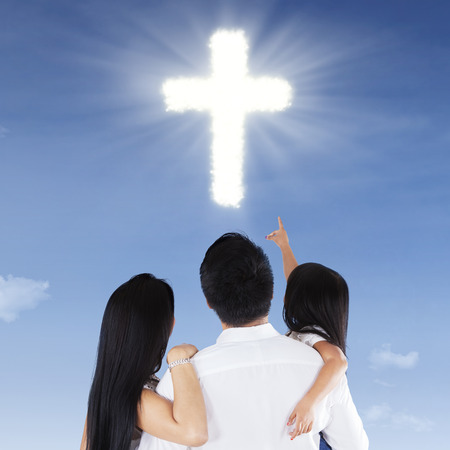 jesus standing: Rear view of family looking and pointing at a cross symbol on the sky Stock Photo