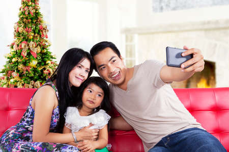 Portrait of asian family sitting on sofa and use a smartphone to take a self photo together photo