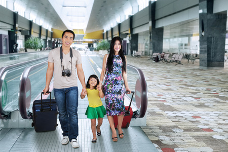 Portrait of asian family carrying luggage and walking in the airport hall for holiday photo