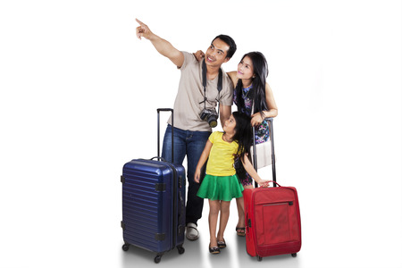 traveller: Portrait of happy family carrying suitcase for holiday and looking at copyspace