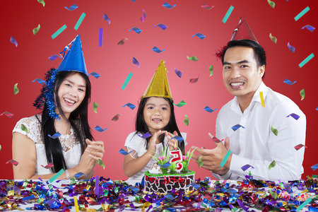 Three member of happy family clap hands and sing together in birthday party photo