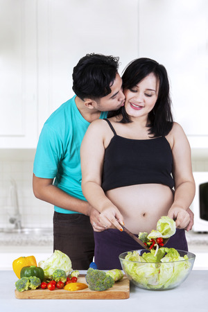 Asian man kiss his wife pregnant when making salad in the kitchen photo