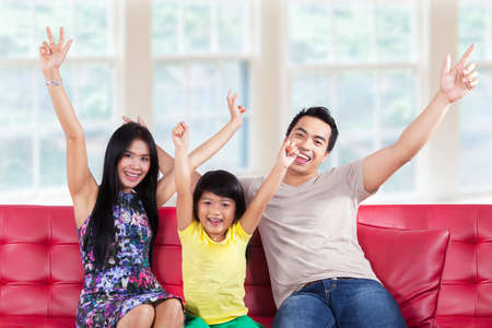 Portrait of asian family sitting on sofa and expressing happy at home photo