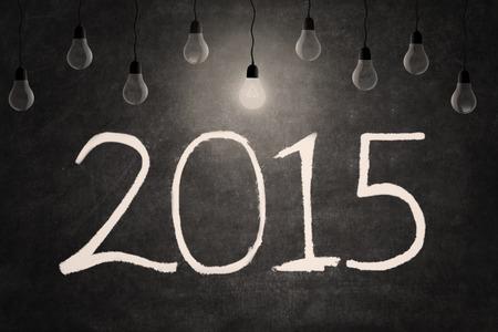 Bright light bulb illuminate the number 2015 on blackboard photo
