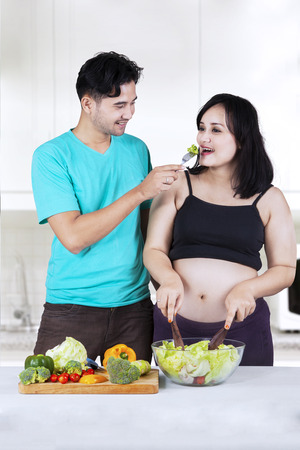 Young asian man giving broccoly with fork to his wife in the kitchen photo