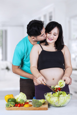 Portrait of asian husband kiss his pregnant wife in the kitchen photo