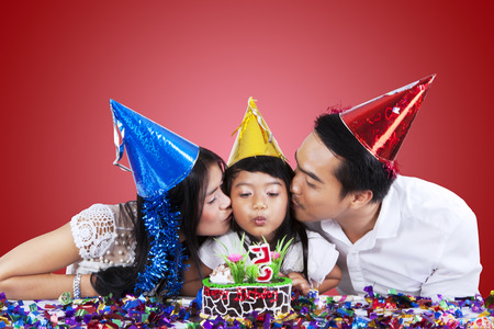 Portrait of two asian parents kiss their daughter when she blowing the candle on birthday cake photo