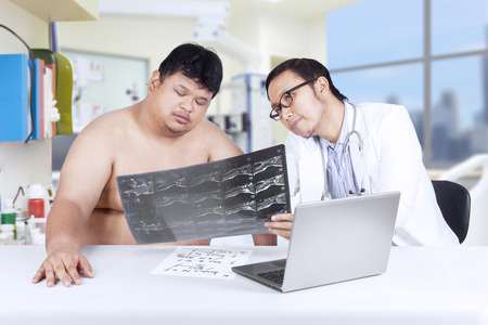 Portrait of asian physician showing and explaining x-ray to overweight person photo