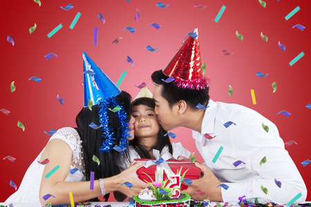 surprise party: Portrait of asian parents kissing their child while giving a gift in birthday party Stock Photo