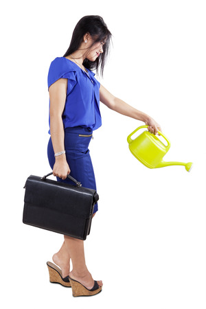nourish: Businesswoman holding a briefcase and a watering can for nourish her business