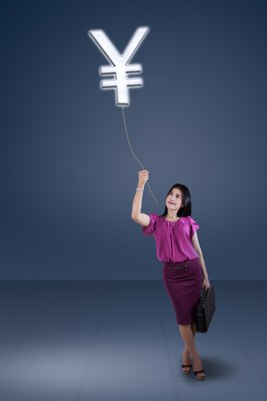 Portrait of businesswoman pulling a Yuan currency, symbolizing growing income photo