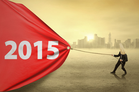 Anonymous person pulling number 2015 on a big banner in the morning photo
