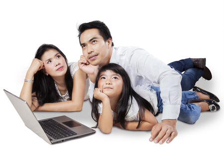 Three member of happy family with laptop computer and dreaming something