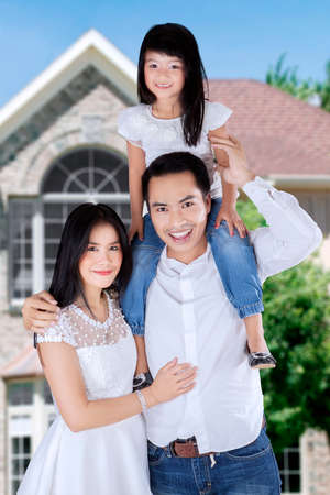 Happy family standing in front of new house while smiling at camera photo