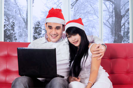 Portrait of happy couple sitting on sofa while wearing santa hat and using laptop for shopping online in winter day photo