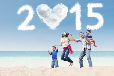 Portrait of attractive family jumping at beach under cloud of 2015 photo