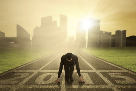 successful business: Man kneeling on track and ready to chase his dream in the future 2015 Stock Photo