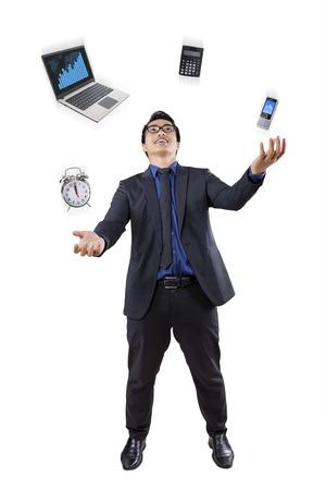 ejecutivos: De longitud completa de empresario malabares cuatro elementos de herramientas de negocios en el estudio