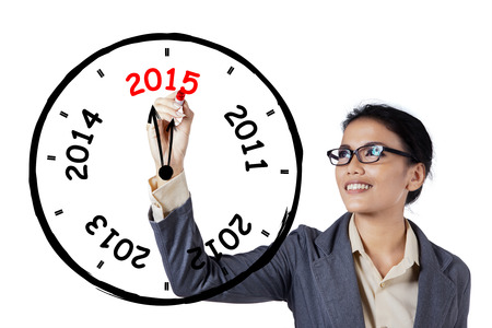 Young businesswoman makes annual clock with number 2012, 2013, 2014, 2015 photo