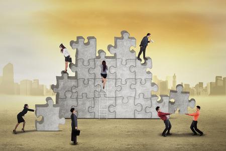 Supervisor looking at her subordinates arrange puzzle, symbolizing leadership and business management photo