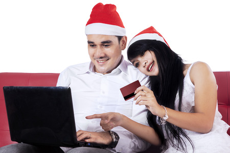 Asian couple holding credit card and use laptop for shopping online in christmas day photo