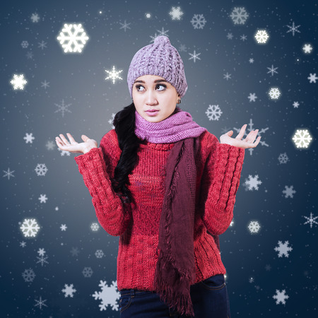 shrugs: Confused winter woman shrugs her shoulders in a clueless gesture Stock Photo