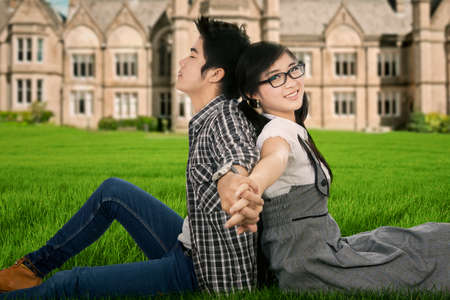 Portrait of two student sitting and holding hands on the university park photo