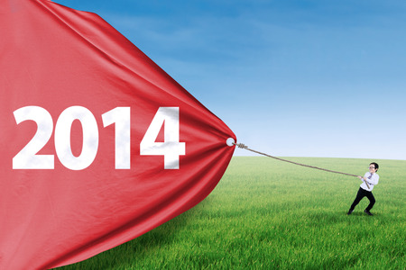 Cute asian boy is pulling big banner of new year 2014 on the meadow photo