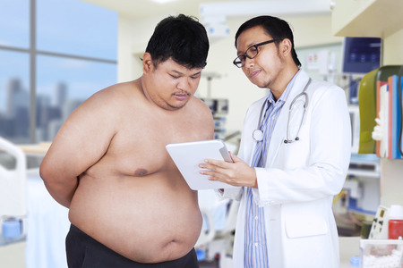 Portrait of hispanic doctor showing the medical notes with a digital tablet to the overweight patient photo