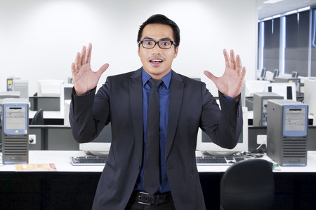 Portrait of asian entrepreneur with shocked expression face, shot in the office photo