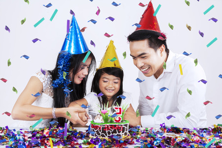 Portrait of happy family celebrate child birthday and cut a birthday cake together photo