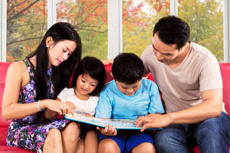 Hispanic family reading a story book together on couch with autumn tree  photo
