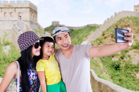 Asian family enjoying holiday and take self portrait together on Great Wall of China photo