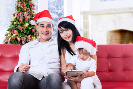 Portrait of hispanic family wearing christmas hat and smiling on camera at home photo