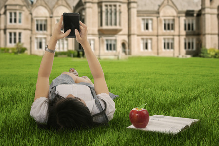 Female student using smartphone for texting on the university park photo