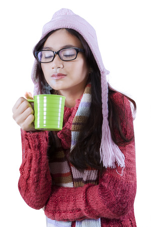 Portrait of pretty asian girl wearing winter clothes and holding a coffee cup in the studio photo