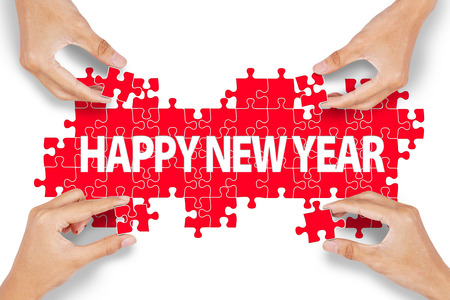 Closeup of four hands playing puzzle and make new year text photo