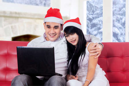 Hispanic couple sitting on sofa and buy online with laptop in christmas holiday photo