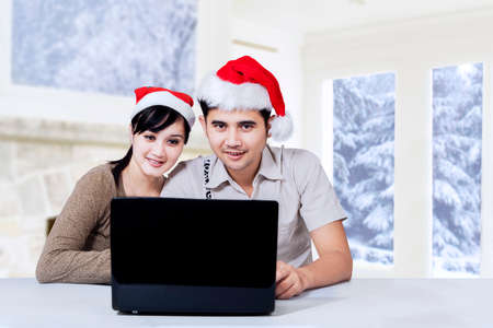 Portrait of happy couple with laptop computer and wearing santa hat at home photo