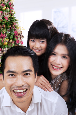 Asian family smiling on camera at home with christmas tree background photo